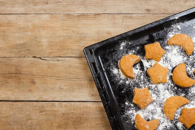 Biscotti fatti a mano su una teglia da forno su una superficie di legno. vista piana, vista dall'alto.