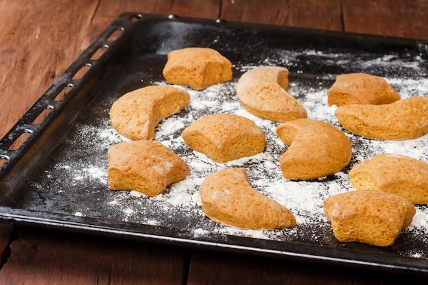 Biscotti fatti a mano sullo strato di cottura su superficie di legno.
