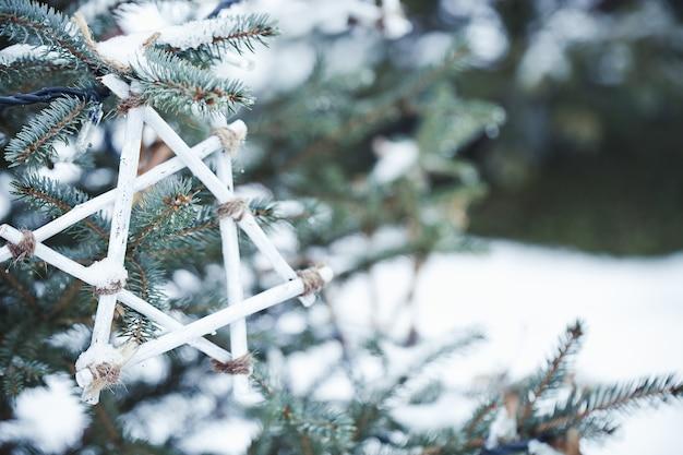 Decorazione fatta a mano su un albero di natale all'aperto nella neve riciclare e concetto di zero rifiuti