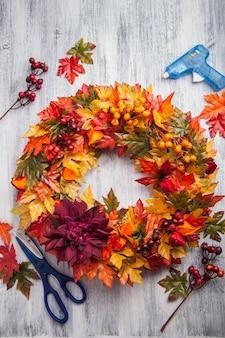 Decorazione artificiale fai-da-te fatta a mano della corona di autunno con il fiore della bacca delle foglie