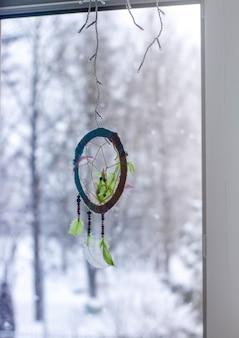 Acchiappasogni fatto a mano sullo sfondo della finestra in una giornata invernale. elemento decorativo tribale. decoro fatto di perline colorate e piume