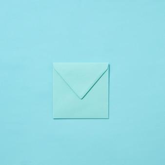 Busta fatta a mano per biglietto di auguri o lettera d'amore su uno sfondo blu pastello con spazio di copia. vista dall'alto.