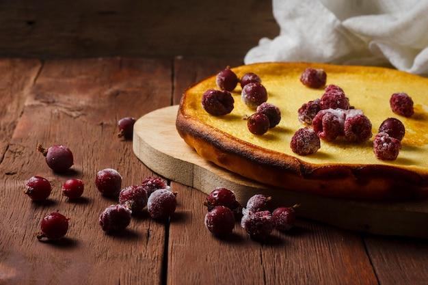 Torta di frutta fatta a mano su una teglia e una tazza con tè caldo o caffè su una superficie di legno. il concetto di abilità culinarie fatte in casa.