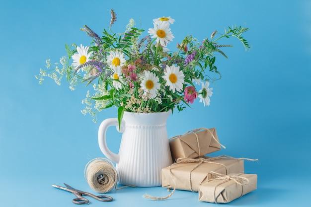 Scatola regalo fatto a mano con fiori di campo su sfondo blu