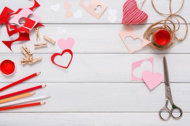 Biglietto di auguri regalo fatto a mano che crea, taglia e incolla, carta artigianale, feltro e strumenti fai da te su legno bianco