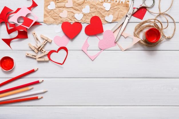 Cuore di auguri regalo fatto a mano che crea, taglia e incolla, carta artigianale e strumenti fai da te su legno bianco