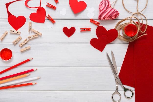 Cuore di auguri regalo fatto a mano che crea, taglia e incolla, carta artigianale, feltro e strumenti fai da te su legno bianco