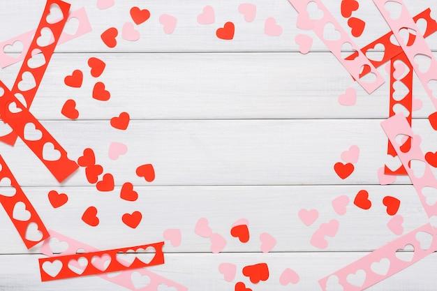 Cuore rosso regalo fatto a mano che crea, taglia e incolla, carta artigianale e strumenti fai da te su legno bianco