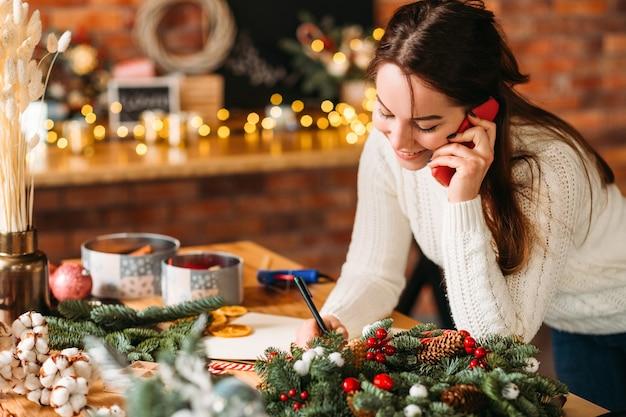Negozio di articoli da regalo fatti a mano. gentile signora che riceve l'ordine per telefono.