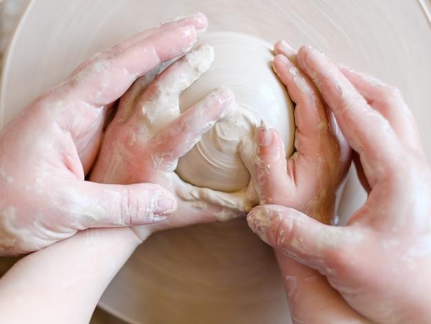 Corsi di ceramica artigianale artigianale. master class in officina. vasaio che forma argilla sulla ruota che gira con un ragazzino studente