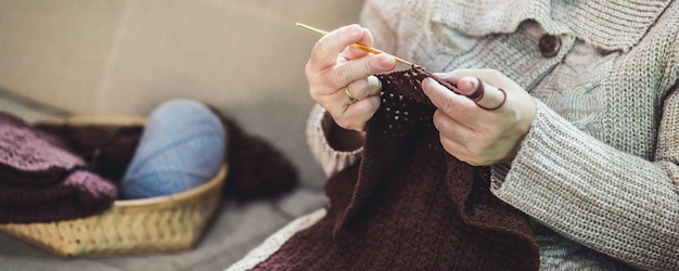 Hobby fatto a mano stare a casa concetto, felice asiatica vecchia donna maglia marrone sciarpa all'uncinetto e tablet sul divano nel soggiorno di casa
