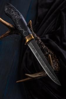 Il coltello da caccia fatto a mano in acciaio di damasco giace sulle corna