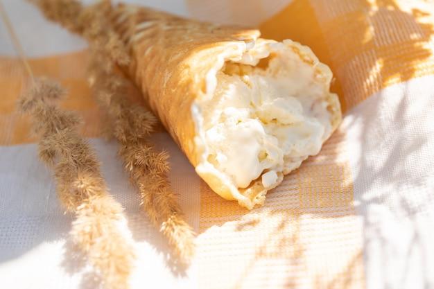 Gelato artigianale in cono di cialda su tovagliolo di lino in una calda giornata estiva concetto estivo