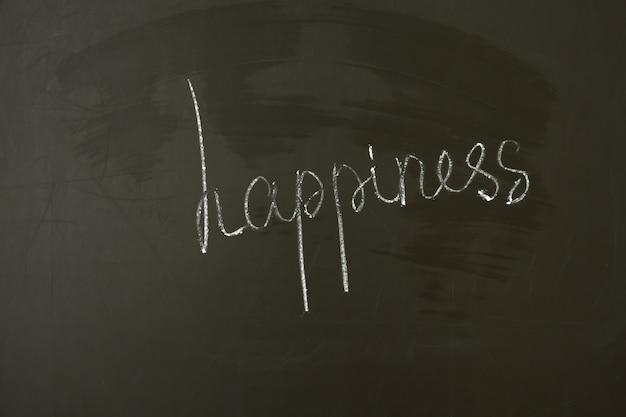 Iscrizione fatta a mano sul concetto di felicità della lavagna