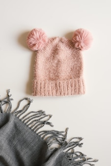 Cappello lavorato a maglia fatto a mano di colore rosa con due divertenti pompon e sciarpa di lana di colore grigio su sfondo bianco, vista dall'alto. abbigliamento caldo per la stagione autunnale e invernale