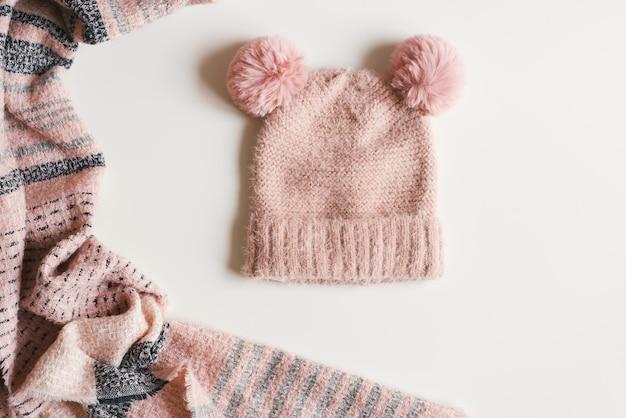 Cappello lavorato a maglia fatto a mano con due pompon e sciarpa calda di colore rosa su sfondo bianco, vista dall'alto. abbigliamento per la stagione autunnale e invernale