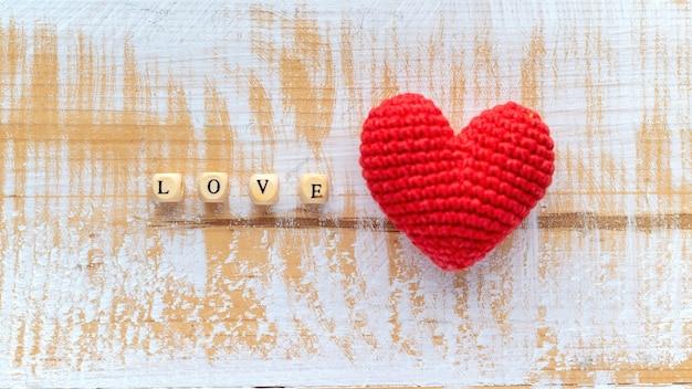 Cuore rosso lavorato a maglia a mano con lettere in legno che compongono la parola amore. vista dall'alto