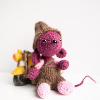 Giocattolo fatto a mano a maglia. un ratto all'uncinetto con una moto gialla