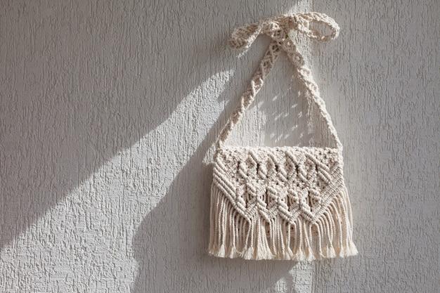 Borsa macramè fatta a mano sulla parete chiara.