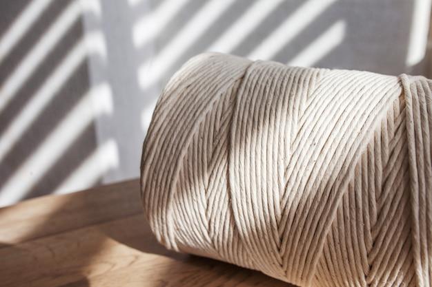 Intrecciatura macramè fatta a mano e fili di cotone da vicino. bobina di filato di cotone per maglieria hobby. hobby femminile