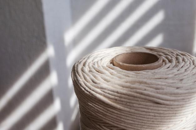 Intrecciatura macramè fatta a mano e fili di cotone da vicino. bobina di filato di cotone per maglieria hobby.