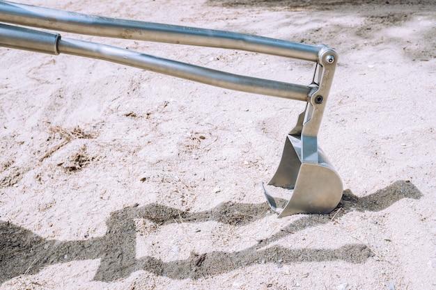 Un escavatore in metallo fatto a mano per i bambini e per esercitarsi a divertirsi con la sabbia.
