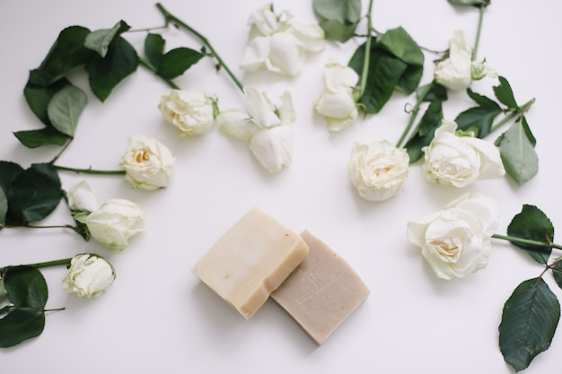 Sapone naturale fatto a mano su sfondo floreale bianco. prodotti cosmetici naturali spa organici su bianco