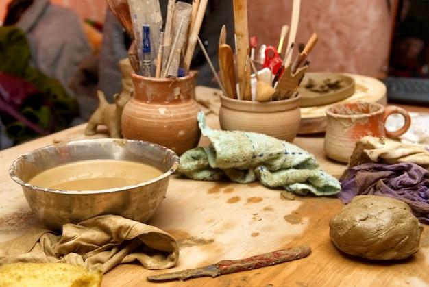 Vecchi vasi di terracotta fatti a mano con matite e altre cose sul tavolo