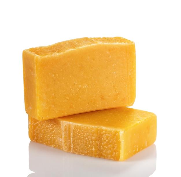 Sapone biologico fatto a mano da prodotti naturali. due saponette con polvere di arancia e ambra su sfondo bianco.