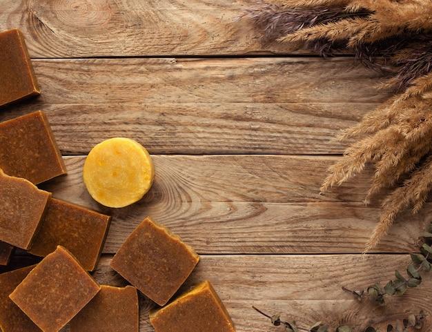 Sapone organico fatto a mano. barre di sapone sul tavolo di legno con fiori secchi.