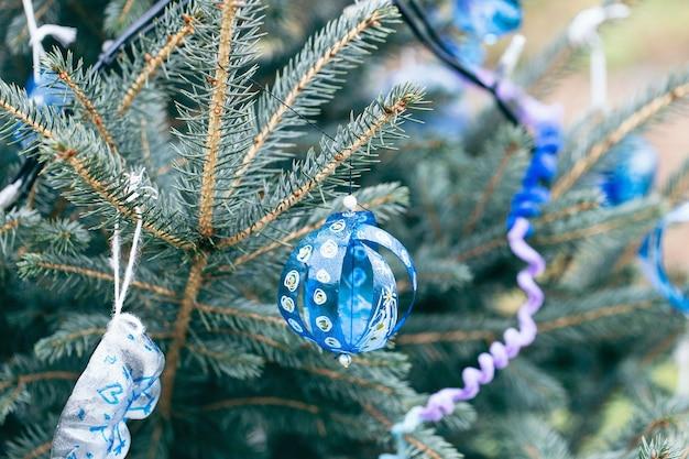 Decorazione dipinta a mano fatta di bottiglia di plastica blu su un albero di natale all'aperto.