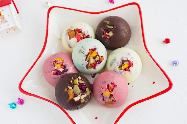 Caramelle di cioccolato rosa, bianche, marroni e selenio fatte a mano con ripieno di noci su un piatto a forma di stella.