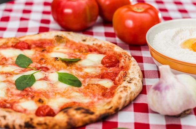 Pizza fatta a mano al sapore di margherita su asciugamano a quadretti stile italiano con diversi ingredienti.