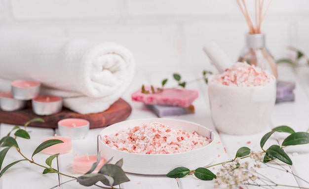 Scrub artigianale alla pesca al sale con olio di argan. sale dell'himalaya. articoli da toeletta, spa set con candele e asciugamano bianco.