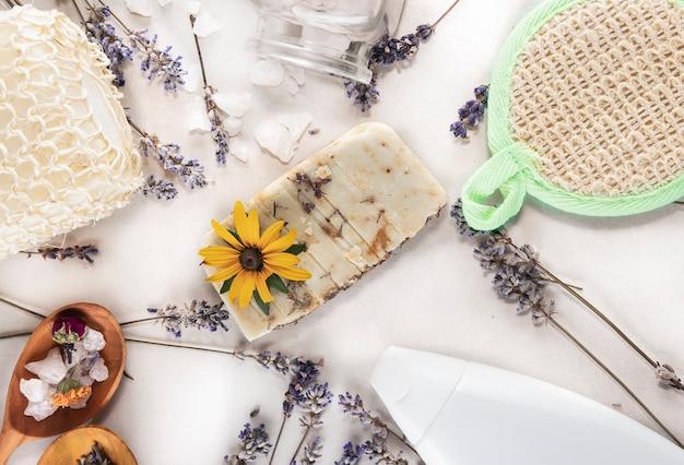 Sapone fatto a mano da erbe e oli salviette lavanda sale marino e una bottiglia di oli per trattamenti termali su uno sfondo bianco