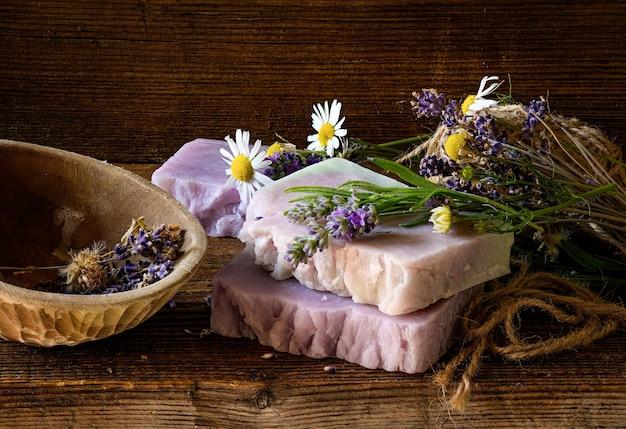 Sapone artigianale con fiori di lavanda e camomilla. natura morta rustica sulla vecchia tavola di legno.