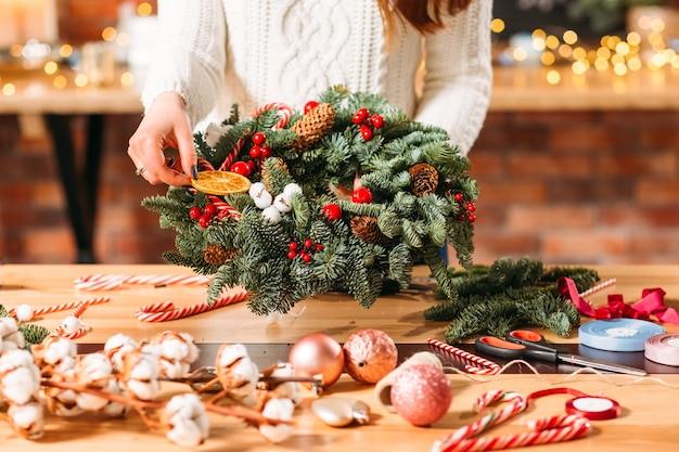 Decorazioni interne invernali fatte a mano. signora che tiene la corona di albero di abete verde.