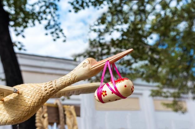 Modello in legno fatto a mano di una cicogna con un bambino nel becco alla mostra di artigianato popolare