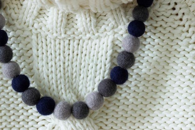 Collana di lana fatta a mano sullo sfondo dei vestiti. messa a fuoco selettiva.