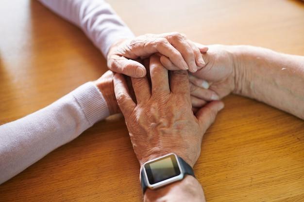 Mani di affettuoso uomo anziano e donna sulla tavola di legno che simboleggia solidarietà e amore