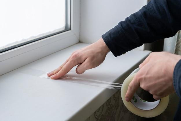 Mani che applicano nastro adesivo sulla superficie