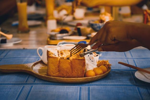 Le mani stanno tagliando su pane tostato al miele.