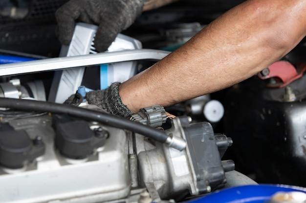 Mani del meccanico che riparano il motore di automobile in garage