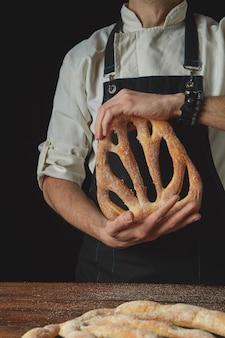 Nelle mani di un panettiere di fougas fresco biologico su uno sfondo scuro