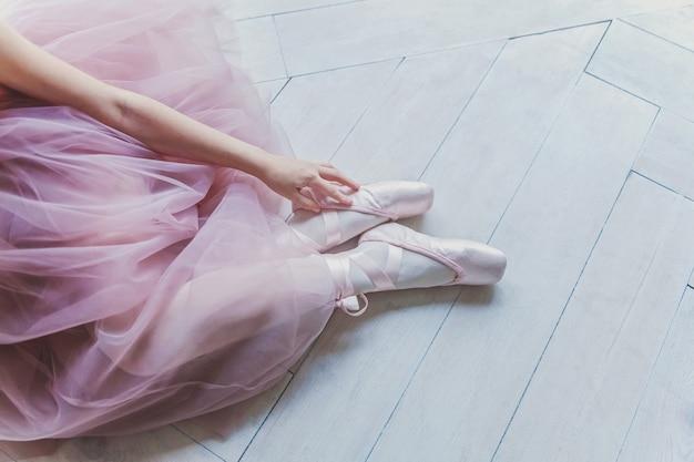 Mani della ballerina in gonna tutu rosa indossa scarpe da punta sulla gamba nel corridoio di luce bianca