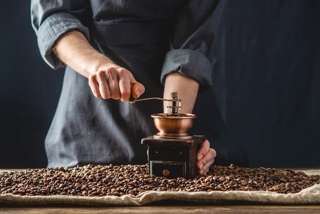 Le mani dei baristi in un grembiule scuro macinano su un macinino manuale fragranti chicchi di caffè