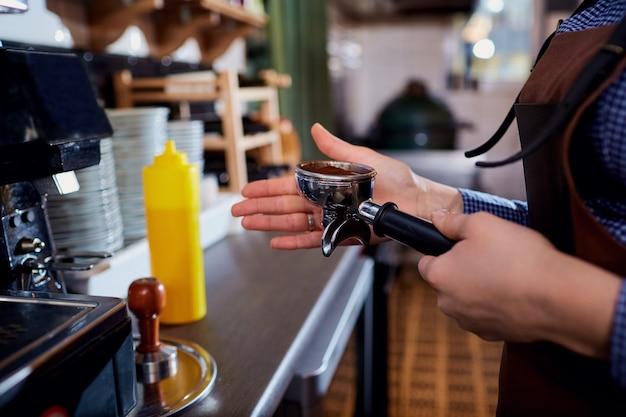 Le mani dei baristi fanno alla macchina del cappuccino al bar