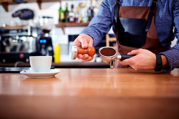 I baristi del barista delle mani fanno il cappuccino al cacao del caffè