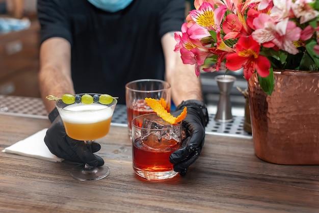 Le mani del barista in guanti protettivi servono cocktail barista non identificato che prepara cocktail