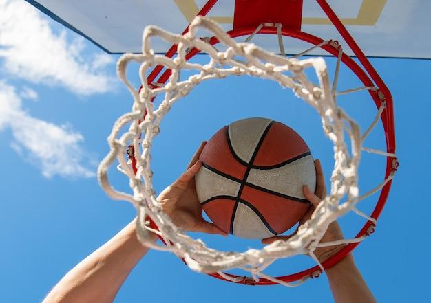Le mani del giocatore di basket lanciano la palla nel cerchio, successo.